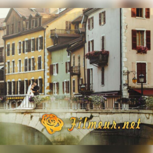 logo filmeur.net sur fond de mariés posant devant le palais de l'isle à Annecy. Photographe de Mariage Annecy.